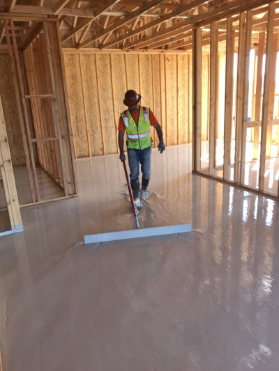 Insul-Flow employee applys gypsum flooring in new construction
